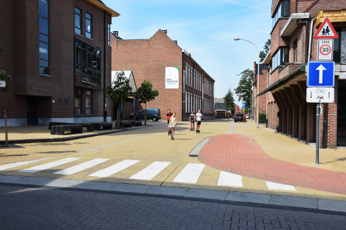 Coloured with iron oxide pigments from CATHAY INDUSTRIES, paving stones for a footpath as well as a driving lane mark the calmed traffic zone in this school area.